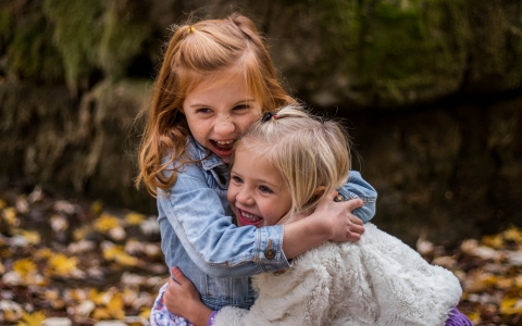 Two little girls smiling and hugging outside