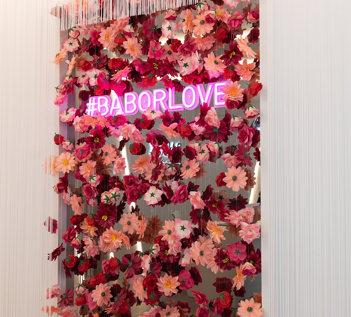 wall of flowers with hashtag babor love in lights