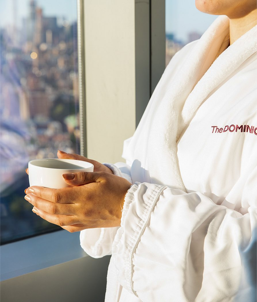 woman wearing a dominick hotel branded robe holding a cup of tea