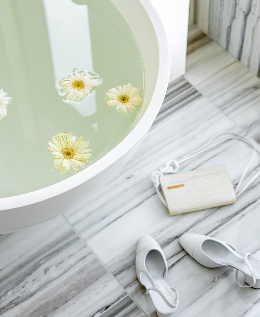 bath tub filled with water and flowers with purse and shoes on the floor