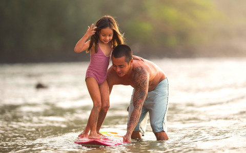 A father teaches his daughter how to surf