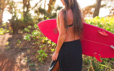 A woman carries a surfboard