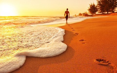 A man leaves footprints on a beach as the sun touches the horizon