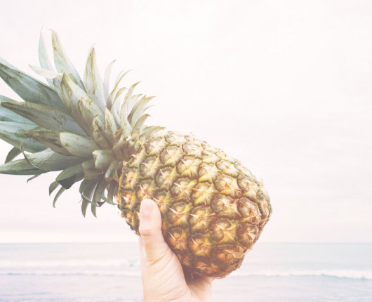 hand holding up a pineapple