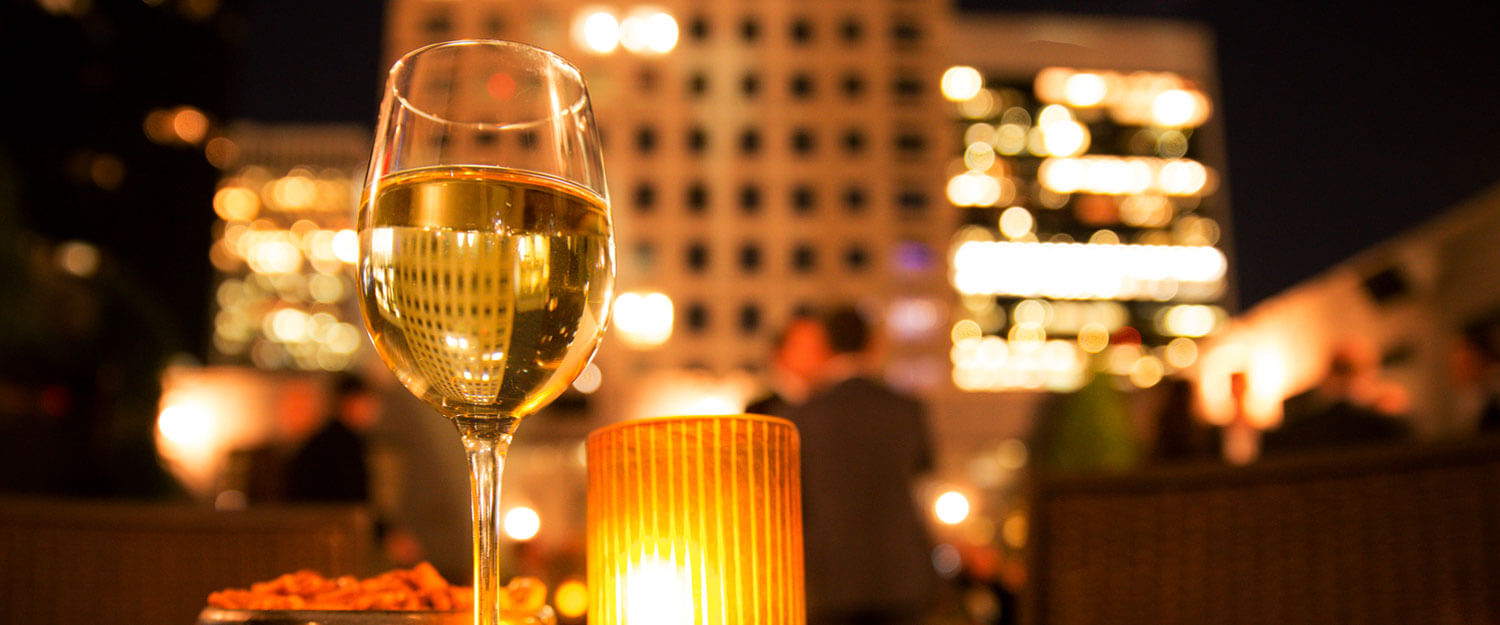 Glass of wine on table with buildings lit up in the background