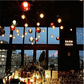 Bar stocked with bottles next to window with city view