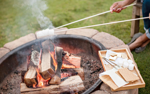 people making smores by a fireplace