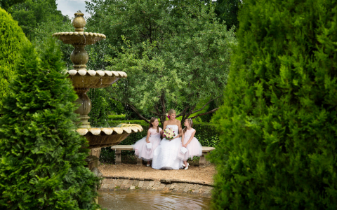 bride and flower girls sitting by a pond in the Barnsley gardens