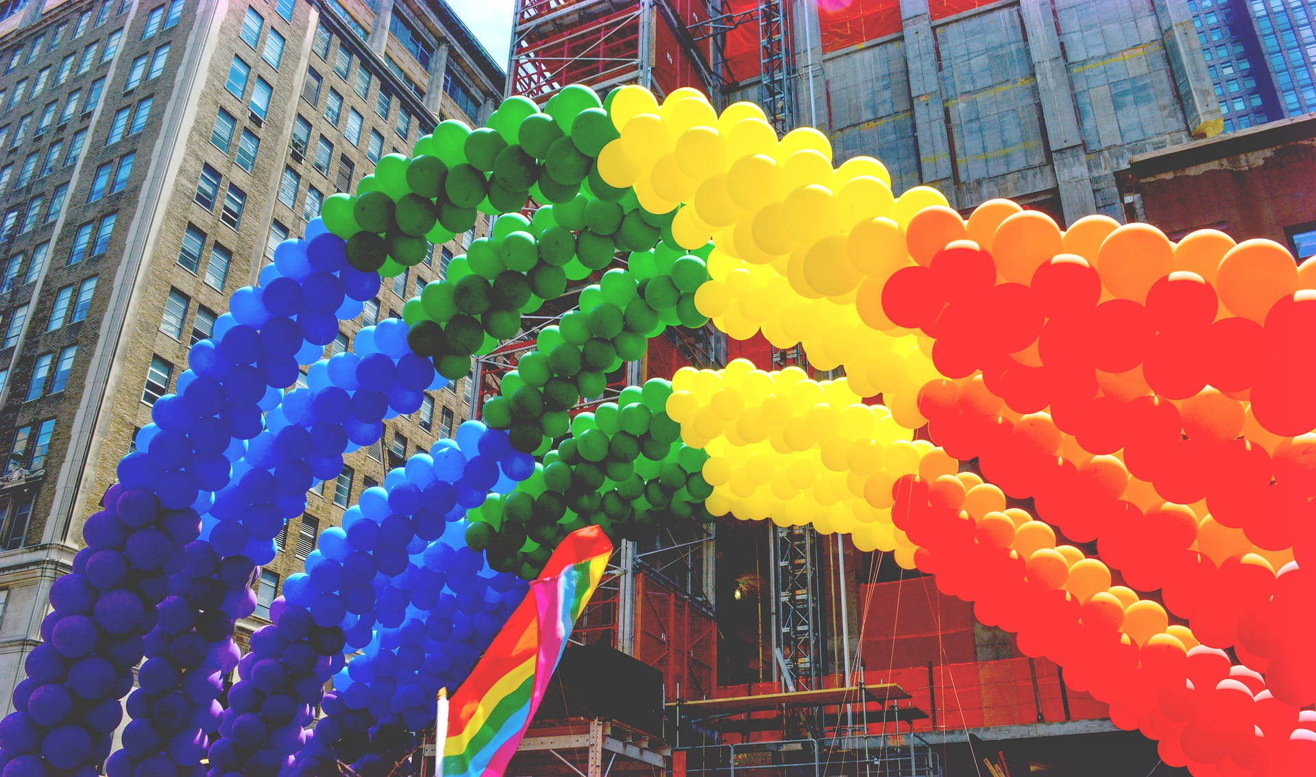 Rainbow pride balloons with tall buildings in background