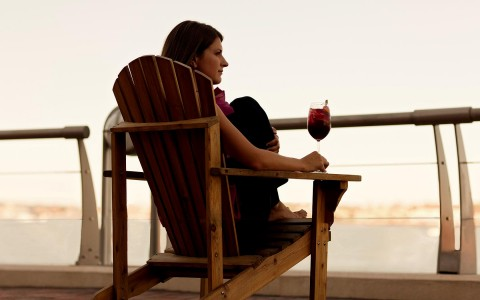 woman sitting outside with a drink