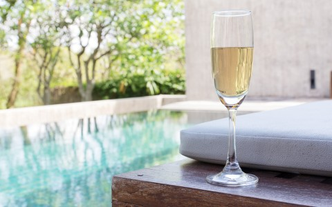 glass of champagne on table near pool