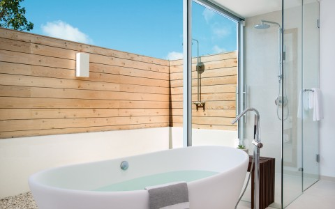 bath tub with floor to ceiling window to private patio
