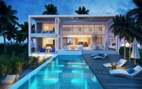 back view of design c villa at night with pool and lounge chairs