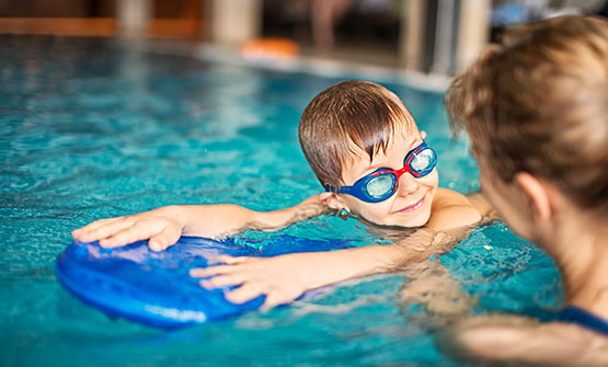 Little boy learning how to swim from instructor at Aquatic Center