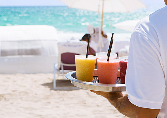 Hotel butler bringing smoothies to guests on beach