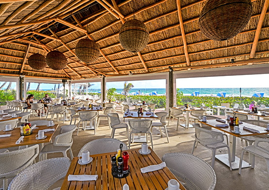 Ocean Grill dining area with wooden tables & wicker chairs