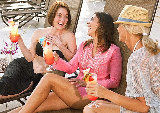 Group of friends laughing while drinking cocktails on loungers