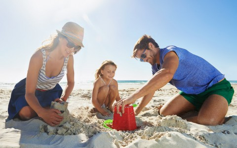 Couple & daughter making sand castles with buckets