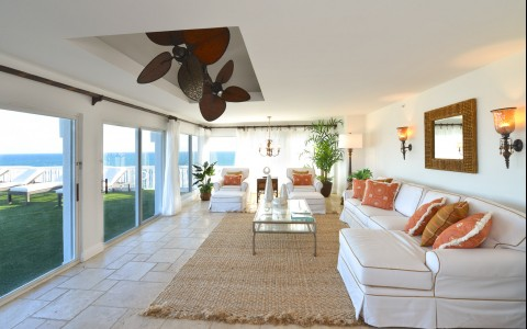 Penthouse living space with white sofas, burlap rug & large window panels with ocean view