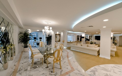 Penthouse room dining space with table, chairs, mirror walls & marble floors