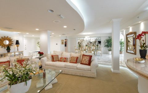 Penthouse living space with glass table, white sofa, red pillows & white columns