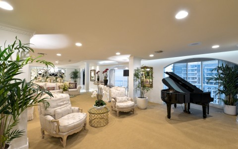 Penthouse living space with cushioned chairs, gold coffee table, plants & grand piano