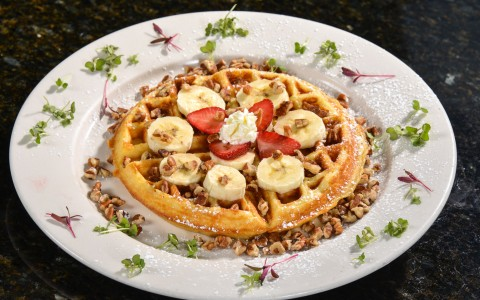 Waffle on plate with nuts, strawberries & bananas