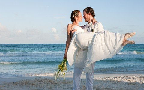 Groom carrying bride on the beach