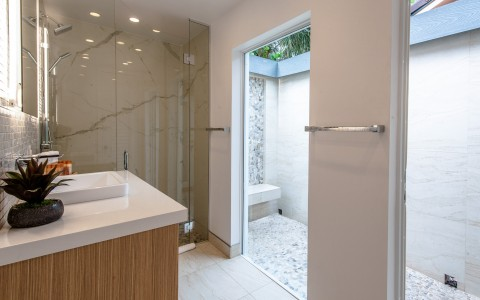 Full bathroom wooden cabinets, white granite, glass shower & outdoor patio access