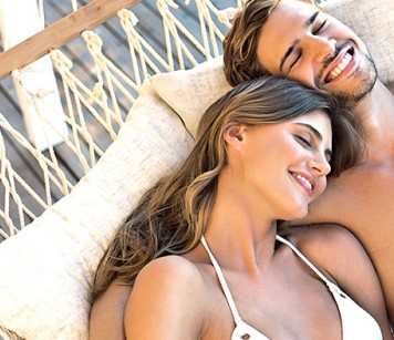Couple laying on hammock with eyes closed