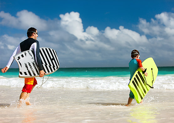Dad and son with boogie boards in water