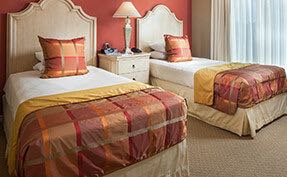 Room with two twin beds, plaid comforters, nightstand and window