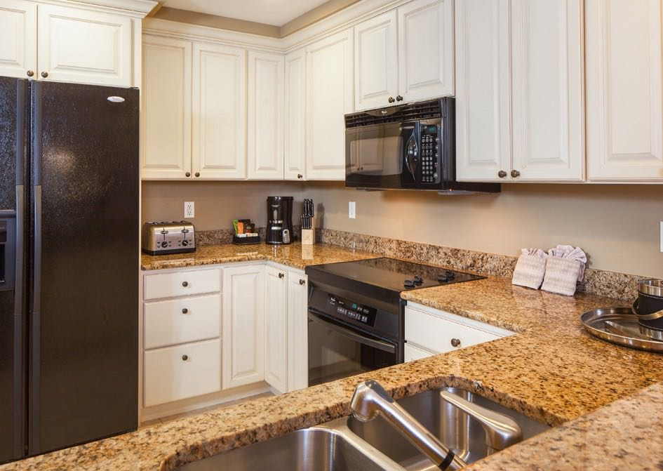 Full kitchen with granite countertops, white cabinets and appliances
