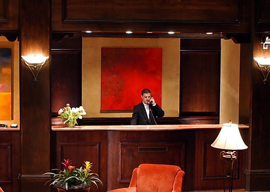 Staff member on phone at wooden front desk