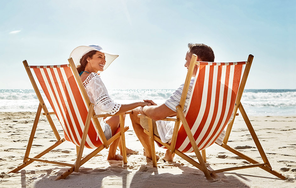 Woman in hat and man sitting in red and white striped chairs on a sunny beach