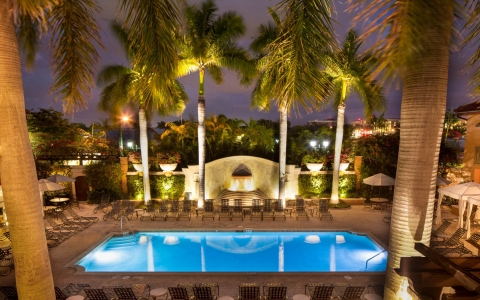 Pool lit up at night with loungers and palm trees