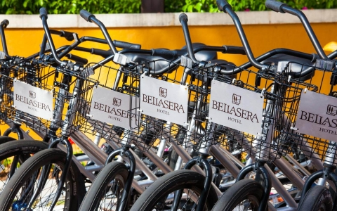 Row of parked bicycles with Bellasera logo on basket