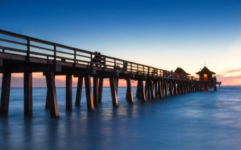 Beach pier on the ocean shore with sun setting in the back