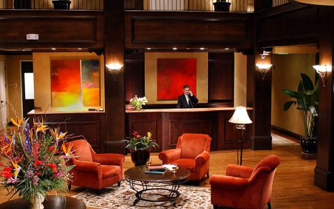 Hotel lobby with red couches, wooden floors, warm lighting & man answering phone at front desk