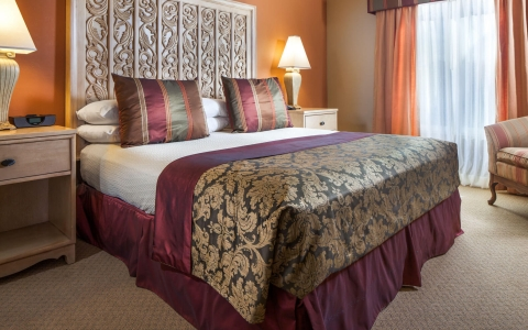 Room with king bed, elegant burgundy comforter, nightstand and window