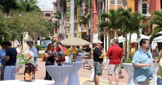 People gathered around cocktail tables in downtown Naples
