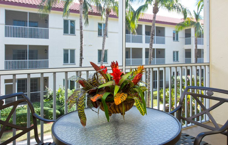 Balcony seating area with tropical leaf arrangement overlooking hotel building on the other side