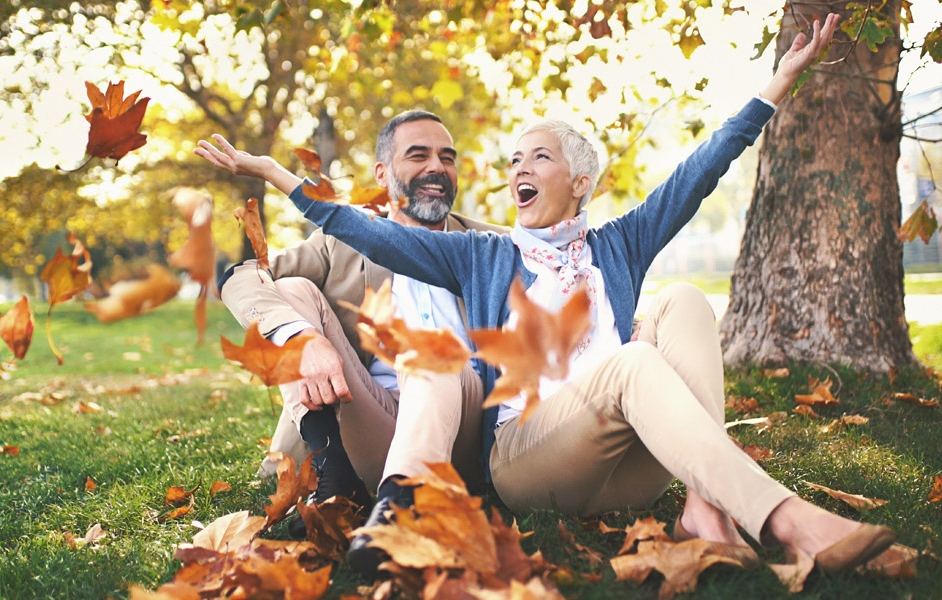 Older couple sitting on grass and throwing fall leaves in the air