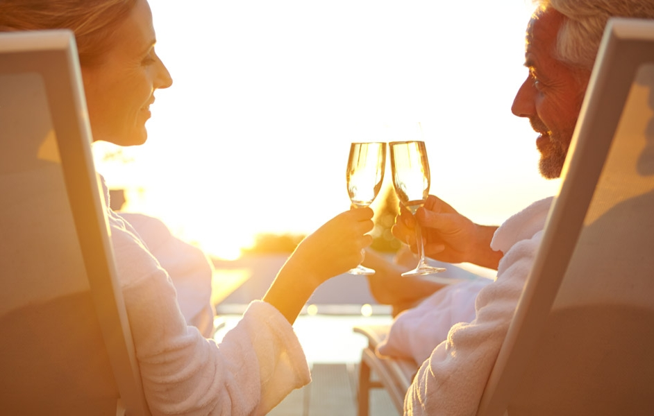 Couple sitting in bath robes outside & toasting with champagne as the sun sets