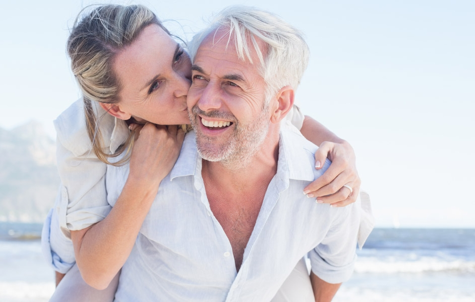 Woman kissing man on cheek from behind with ocean in the back