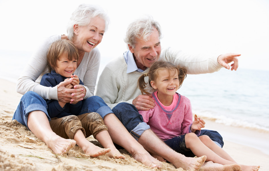 Older couple sitting on sand by the water with young children