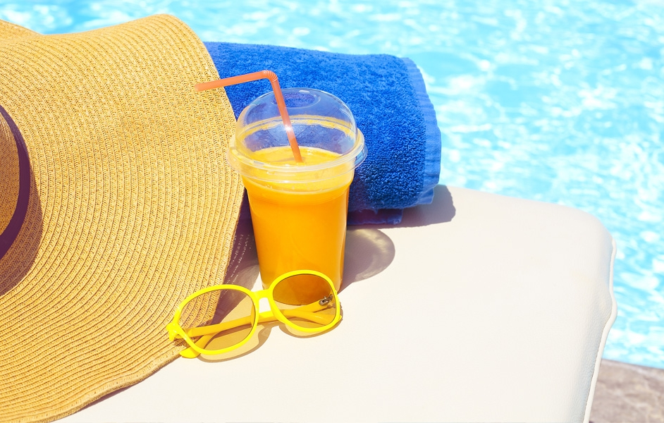 Sun hat, smoothie, sunglasses and towel by the pool