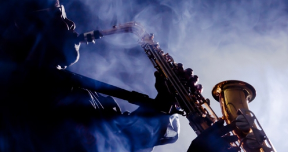 Man surrounded by smoke playing sax on stage