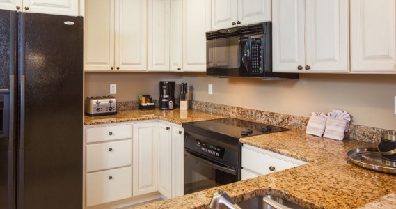 Full kitchen with granite countertops, white cabinets & appliances