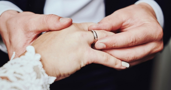 Close up of groom placing wedding band on brides finger